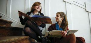 Foto de Leonor Beuter y Maria Rosa Lojo posando en una escalera sosteniendo ejemplares del libro Las Siniguales.